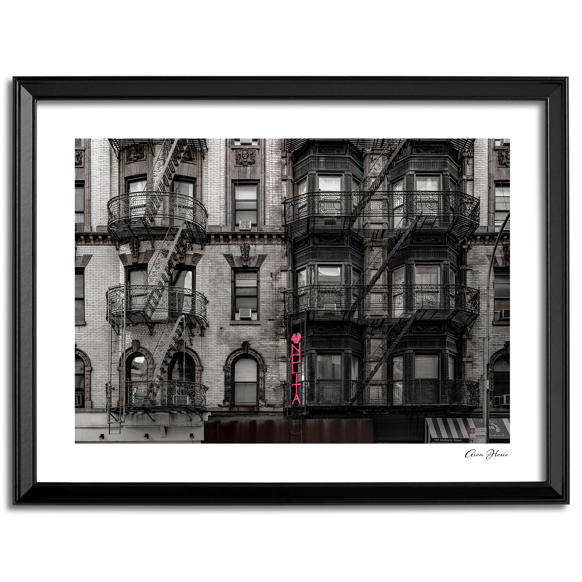 Print of old steel New York fire escapes and pink NOLITA sign.