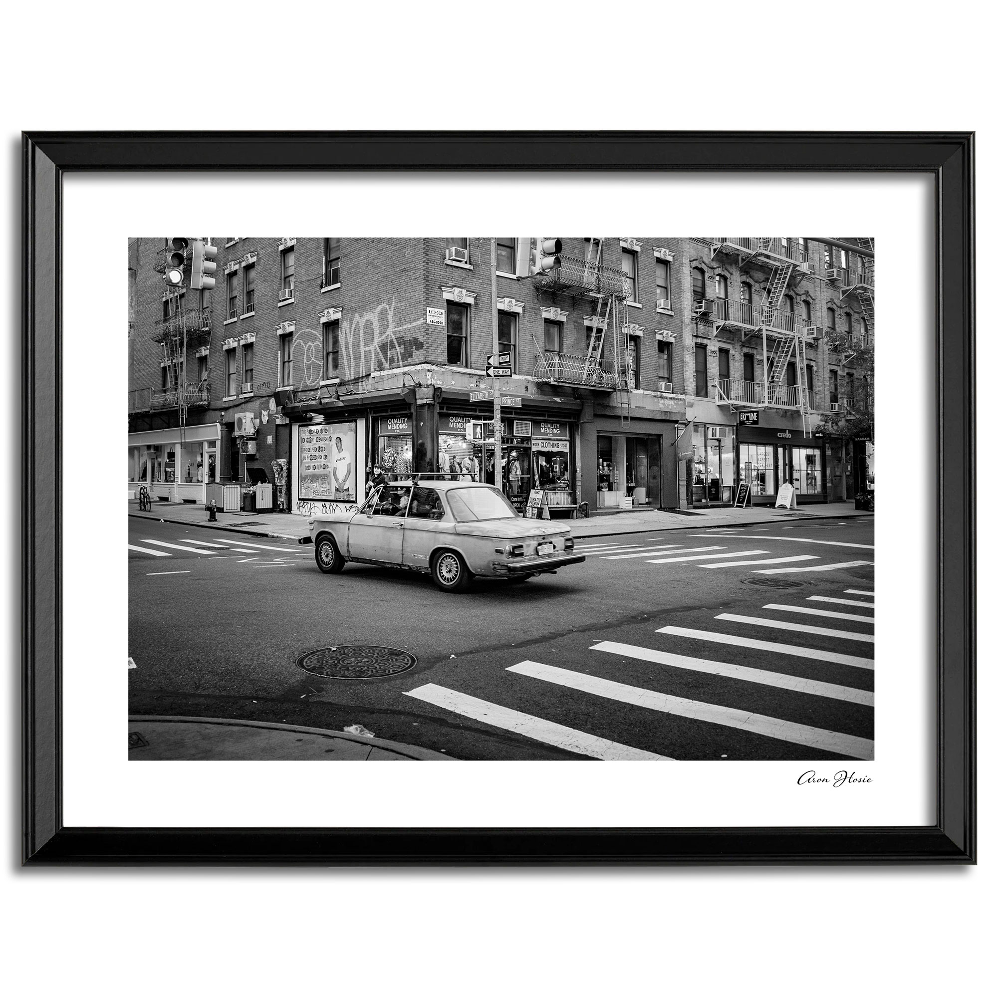 Black and white print of old man in old BMW diving down Elizabeth Street, Manhattan.
