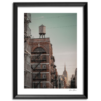 Print of a water tower sitting on top of a building with the Empire State Building in the background